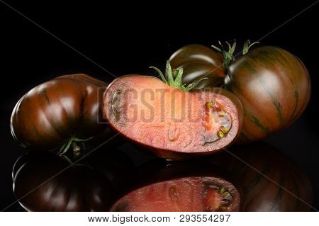 Group Of Two Whole One Half Of Meaty Fresh Tomato Primora Isolated On Black Glass