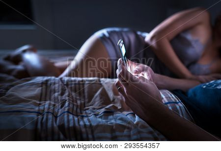 Man Using Smartphone And Ignoring Sexy Woman In Bed At Night. Looking At Mobile Phone. Husband Givin