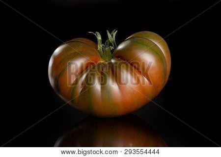 One Whole Meaty Fresh Tomato Primora Isolated On Black Glass
