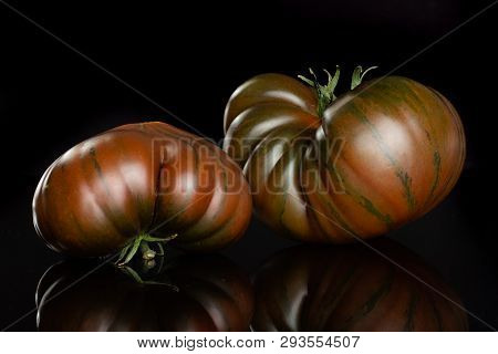 Group Of Two Whole Meaty Fresh Tomato Primora Isolated On Black Glass