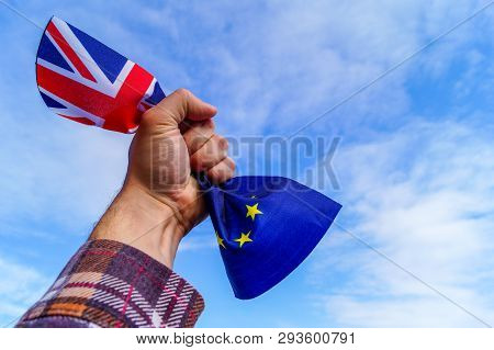 A Male Hand Holds In His Fist The Flags Of England And The European Union Against A Blue Sky And Sym