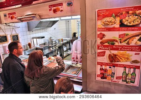 Berlin, Germany - August 25, 2014: People Order Curry Wurst Sausages In Berlin. Currywurst Is A Trad