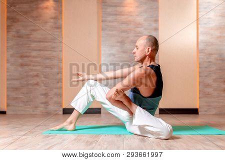 Adult man practicing yoga sitting on blue mat.