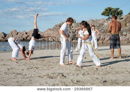 Group of people practice Capoeira on beach.