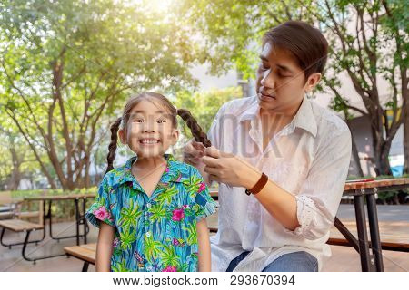 stepfather concept daddy love daughter do pigtail hair for kid at park in morning. Lovely moment of family. poster