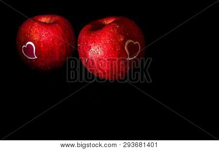 Heart Shape Sticker And Water Droplet On Glossy Surface Of Red Apple On Black Background