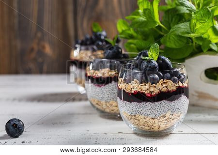 Light Dessert Of Chia Pudding With Blueberry, Oats And Fresh Jam, Served In Thin Glass.