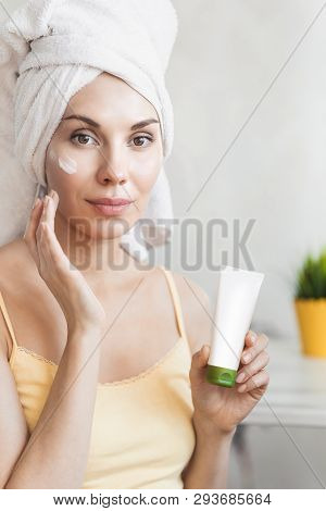 Girl Applies Face Cream. Skin Care And Beauty Concept. Young Woman Applying Moisturizer On Her Face.