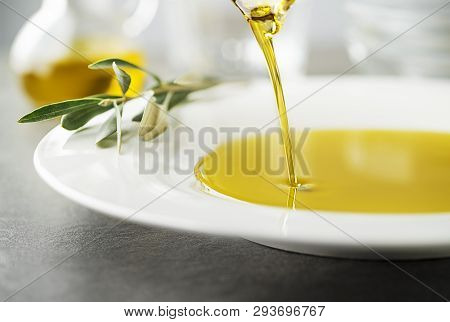 Bottle Of Healthy Virgin Olive Oil Pouring To Plate Close Up. Healthy Background Concept