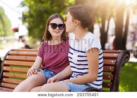 Two Creative Girls Talk And Laugh While Sitting On Bench Outdoors. Young And Funloving Friends Share