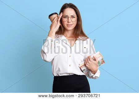 Tired Young Girl Holds Her Hand With Coffee Near Temple, Has Bunch Of Books In Hand, Feels Unwell, A