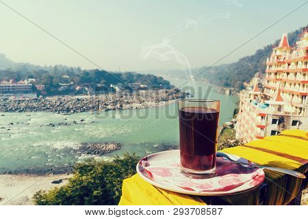 A Glass Of Coffee On A Plate Against The Background Of The Beautiful Scenery Of Rishikesh.. View Of