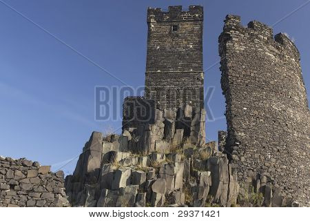Ruin of state castle named Hazmburk which stands on basalt black rock. Blue sky in the background (Czech Republic) poster