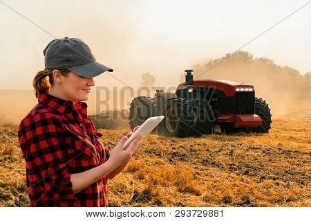 Woman  Farmer With Digital Tablet Controls An Autonomous Tractor On A Smart Farm