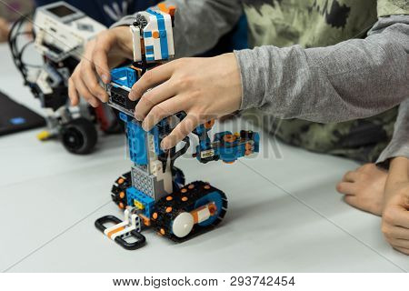Group Of Kids Building Robot Constructor From The Plastics Details Programmed On The Computer, At Ro