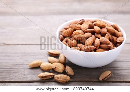 Bowl of almonds on a grey background poster