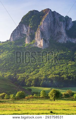 Wonderful Romania Countryside At Sunrise. Huge Rocky Formation On Top Of A Forested Hill. Trees On A