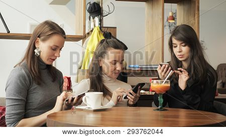 Three Women Girlfriends In A Cafe Are Browsing Their Mobile Phones. Friendly Meeting In The Cafe. Fr