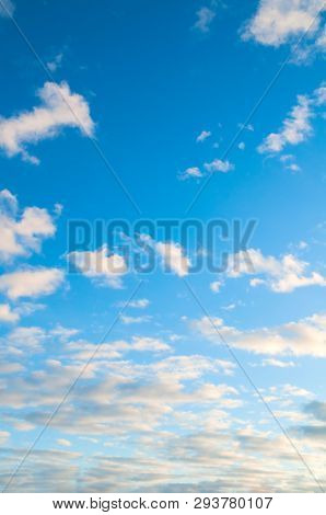 Sky background. Blue sky landscape with dramatic sundown clouds lit by evening sunset sky light, colorful sky background, cloudy sunset sky view