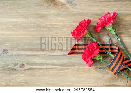 9 May background - red carnations and George ribbon lying on the wooden background, free space for festive 9 May text