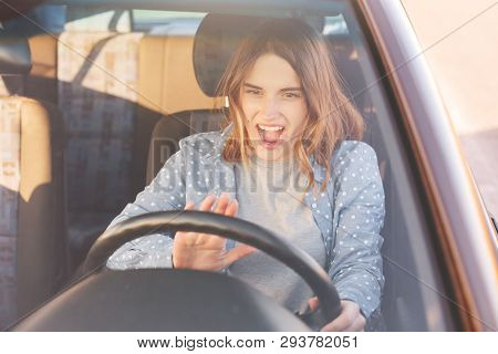 Portrait of beautiful young woman in new car, driving her automobile first time, beeps to her husband happillly, has wonderful present for her birthday. Attractive female enjoys of buying vehicle. poster