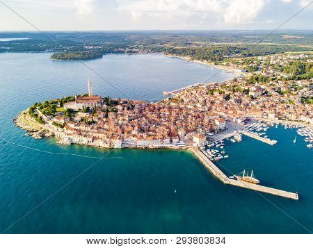 Croatian town of Rovinj on a shore of blue azure turquoise Adriatic Sea, lagoons of Istrian peninsula, Croatia. High bell tower, red tiled roofs of historical buildings, sailboat, piers. Aerial view. poster