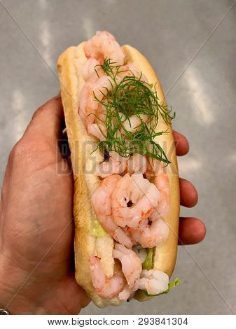Shrimp Sandwich With Dill Holding In Hand. Seafood.