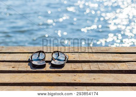 Pair Of Flip Flops On The Wooden Dock And Scenery Of Lake River At Natural Background.