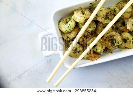 Cooked Garlic King Prawns With Herbs And Butter Sauce With Chopsticks In A White Dish.