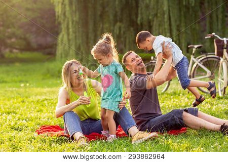 Young Family With Little Children Having Fun In Nature