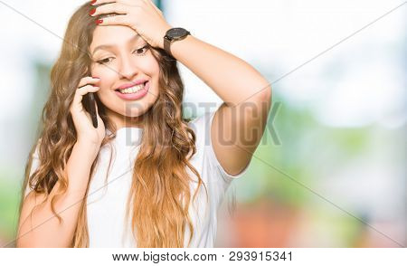 Young adult woman taking on the phone stressed with hand on head, shocked with shame and surprise face, angry and frustrated. Fear and upset for mistake.