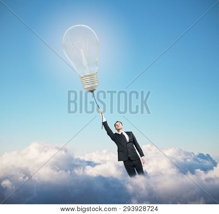 Businessman With Glowing Lamp Flying On Blue Ske With Clouds Background. Idea Concept