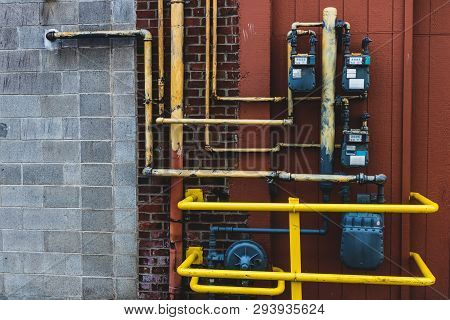 Gas And Electrical Meters With Bright Yellow Pipes And Cage