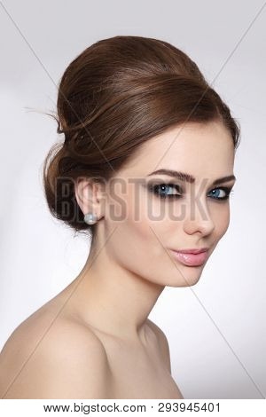Vintage style portrait of young beautiful woman with fancy hair bun and smoky eye makeup