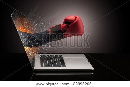 Hand with boxing gloves coming out of a laptop with sparkling effects