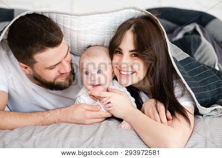 Young Smiling Family With Infant Under Blanket