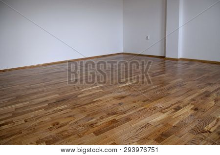 Empty Room, White Mortar Wall Background And Wood Parquet Floor In Residential. Parquet Floor Close