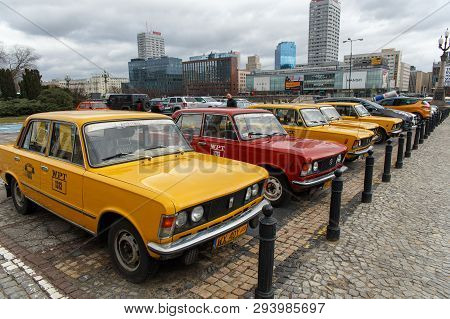 Warsaw, Poland - Mart 10, 2019: A Row Of Yellow And Red Retro Taxi, A Polski Fiat 125p On Parking Ne