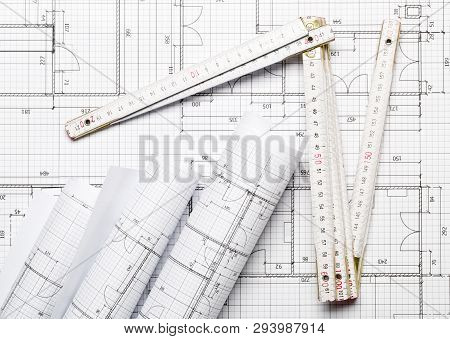 Rolls Of Architectural Blueprint House Building Plans On Blueprint Background With Folding Rule On T