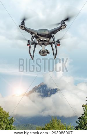Modern Drone Flies In The Mountains. Dark Drone In The Air Against The Backdrop Of A Mountain Landsc