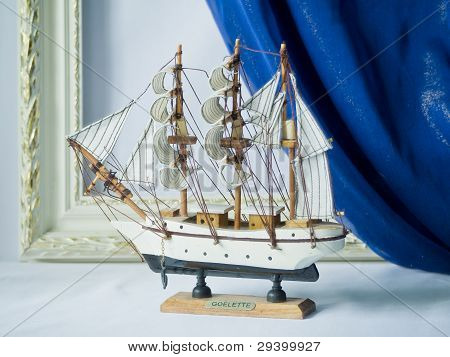 Sailing vessel against a portiere and a frame