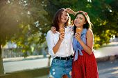Two young female friends having fun and eating ice cream. Cheerful caucasian women eating icecream outdoors in the city. Pretty girls posing with ice-cream. Summer time concept. poster