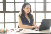 Portrait of smiling pretty young Asian business woman working on laptop in her workstation poster