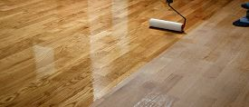 Lacquering Wood Floors. Worker Uses A Roller To Coating Floors. Varnishing Lacquering Parquet Floor