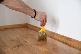 Lacquering Wood Floors. Worker Uses A Brush To Coating Floors. Varnishing Lacquering Parquet Floor B