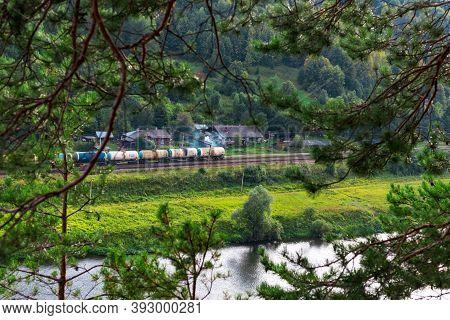 Kungur, Perm Region, Russia - August, 8 2020: Long Multicolored Freight Train Goes Along Chusovaya R