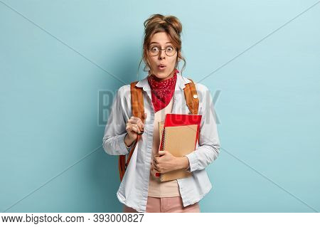 Photo Of Surprised Schoolgirl Holds Notepads, Ready For School And Studying, Carries Rucksack, Impre