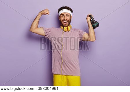 Happy Strong Man Lifts Weight In Sport Gym, Shows Muscles, Glad To Be Fit And Healthy, Wears Casual