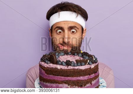 Close Up Shot Of Surprised Guy Stares At Delicious Cake, Feels Temptation, Licks Lips With Tongue, W