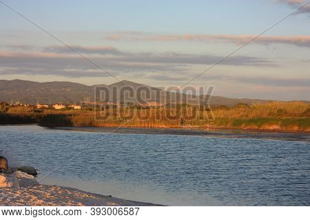 Small Blue Tuscan River Flows Into The Sea Between The Maremma Countryside At The Warm Hour Of The P